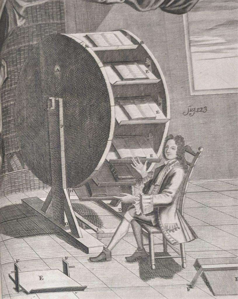 A man sits at a bookwheel.